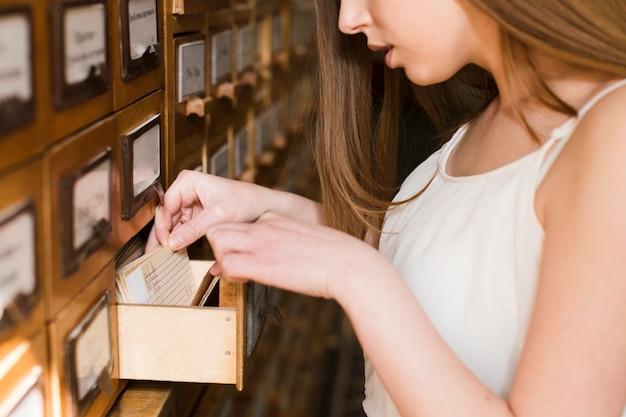Di nuovo al concetto del banco con la fine in su della donna che studia nella libreria