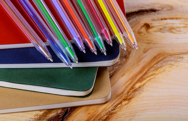 Di nuovo al concetto del banco, penna colorata, fondo di legno del quaderno