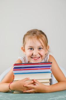 Di nuovo al concetto del banco sulla vista laterale della parete grigia e del gesso. bambina che abbraccia quaderni e libri.