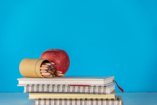 Di nuovo al concetto della scuola apple e materiale scolastico sulla tavola bianca