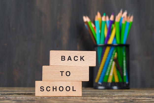 Di nuovo al concetto della scuola con i blocchi di legno, matite in supporto sulla vista laterale della tavola di legno.