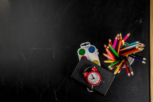 Di nuovo al concetto della scuola con il fondo della lavagna delle matite di colore della sveglia dei libri