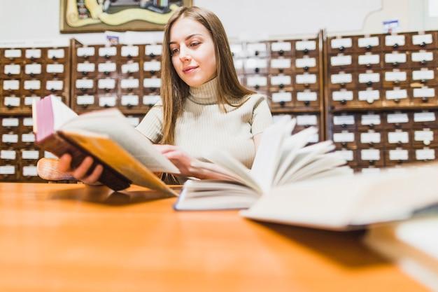 Di nuovo al concetto della scuola con la donna che studia nella biblioteca