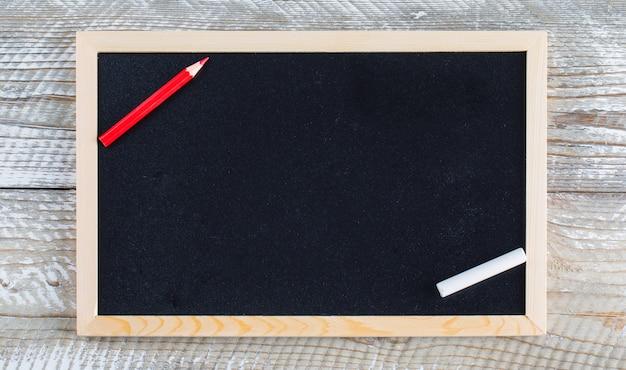 Di nuovo al concetto della scuola con la matita, gesso sulla disposizione piana del fondo di legno.
