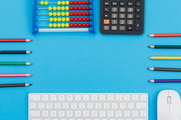 Di nuovo al concetto della scuola con le matite, la tastiera, il topo, il calcolatore, l'abbaco sulla disposizione piana del fondo blu.