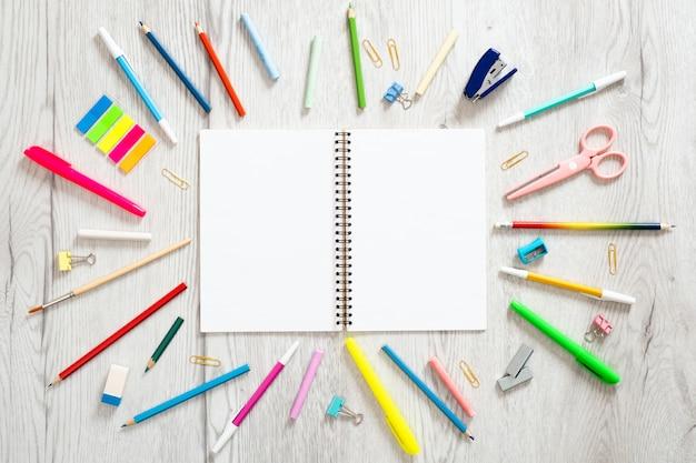 Di nuovo al concetto della scuola, disposizione creativa con con i vari rifornimenti di scuola e blocco note della carta in bianco con lo spazio della copia.