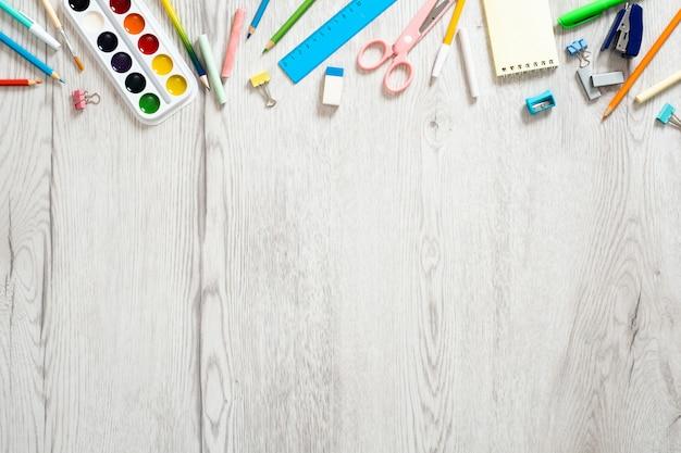 Di nuovo al concetto della scuola, disposizione creativa con con i vari rifornimenti di scuola sul fondo di legno dello scrittorio