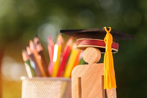 Di nuovo al concetto della scuola, il legno del segno della gente con la scatola di matita della sfuocatura del cappuccio di celebrazione di graduazione.
