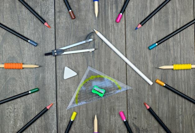 Di nuovo al concetto della scuola: pastelli delle matite e rifornimenti di scuola su un fondo di legno