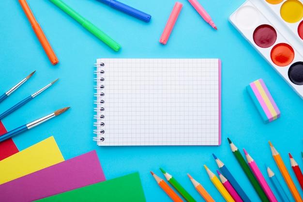 Di nuovo al concetto della scuola su fondo blu con lo spazio della copia