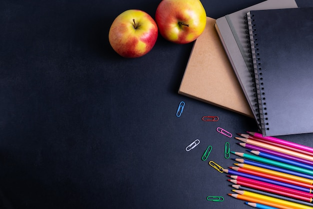 Di nuovo al fondo della scuola con i libri e la mela sulla disposizione del piano della lavagna