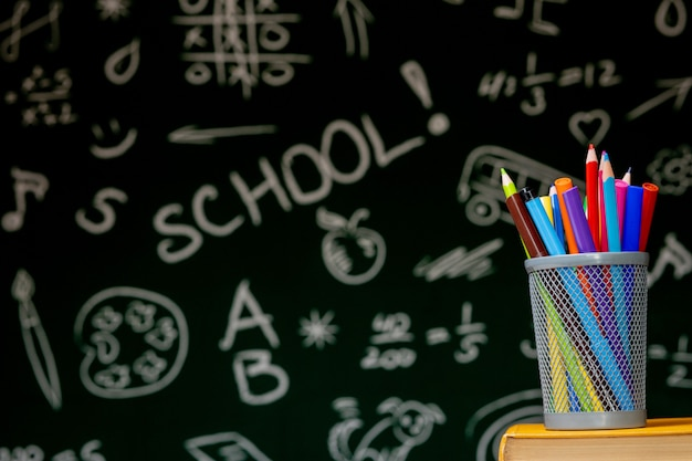 Di nuovo al fondo della scuola con i libri, le matite e la mela sulla tavola bianca.