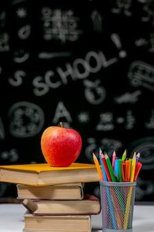 Di nuovo al fondo della scuola con i libri, le matite e la mela sulla tavola bianca