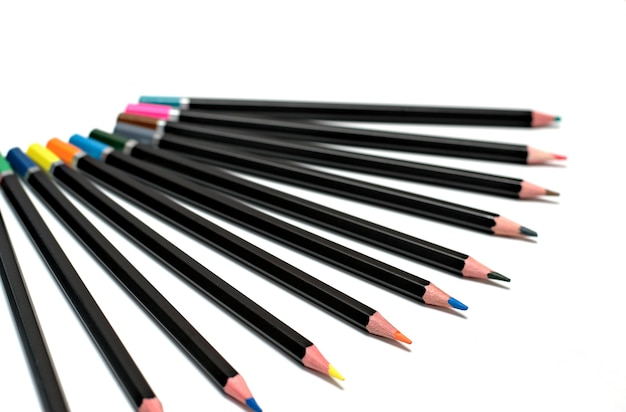 Di nuovo alla scuola concetto-chiuda in su dei pastelli colorati su una priorità bassa bianca.