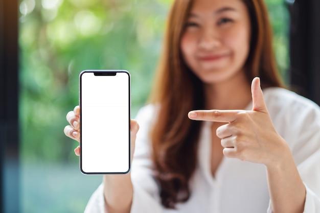 Di una bella donna asiatica che punta il dito contro un telefono cellulare con schermo bianco vuoto, offuscata natura verde