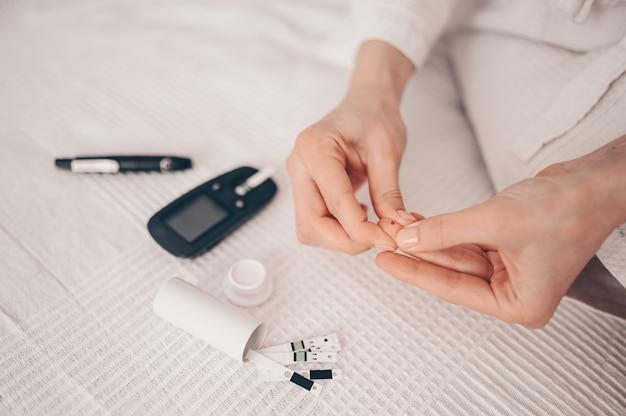 Diabete che controlla il livello di zucchero nel sangue. donna che usando lancelet e glucometer digitale a casa. medicina, diabete dietetico, concetto di sanità - mani femminili con glucometro che controlla il livello di glucosio del corpo