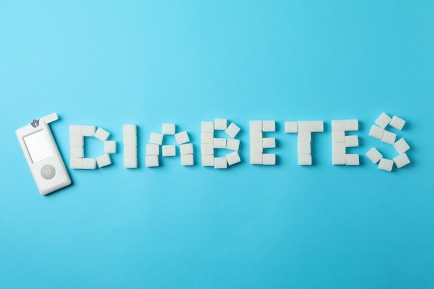 Diabete fatto di zollette di zucchero e misuratore di glucosio nel sangue su sfondo blu