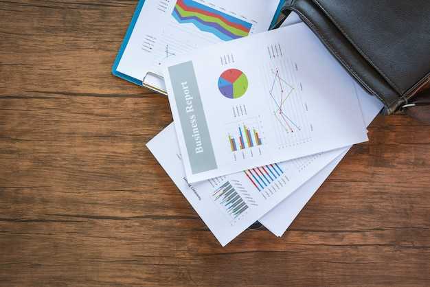 Diagramma del rapporto di affari che prepara i grafici sul sacchetto del briefcase / rapporto di sintesi nel cerchio di statistiche grafico a torta sul documento di affari di carta