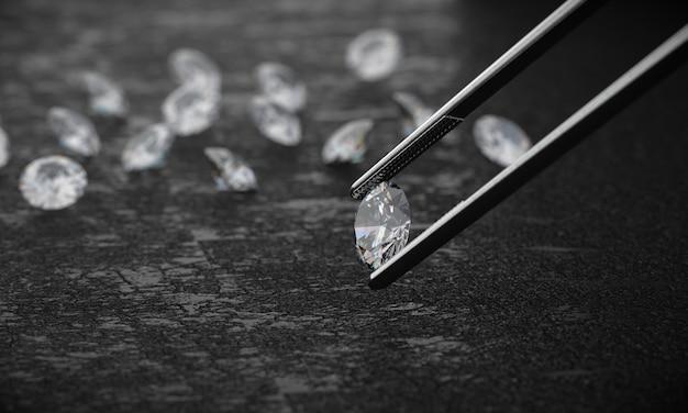 Diamante in pinzetta su uno sfondo scuro con gruppo di diamanti