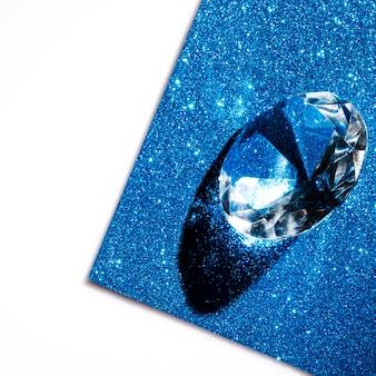 Diamante trasparente in cristallo su fondale scintillante luccicante blu