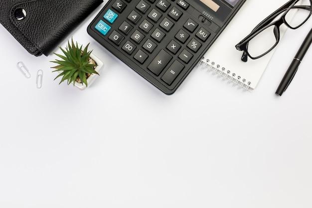 Diario, calcolare, pianta di cactus, blocco note a spirale, occhiali e penna su sfondo bianco