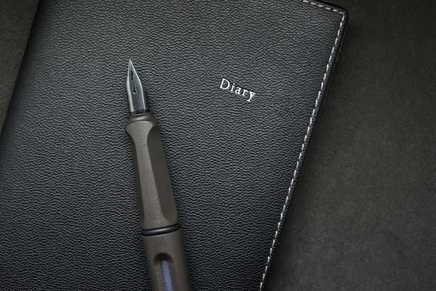 Diario con penna stilografica su sfondo nero