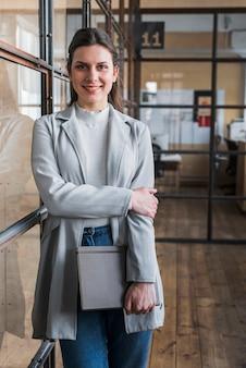 Diario felice della holding della giovane donna di affari che esamina macchina fotografica nel luogo di lavoro