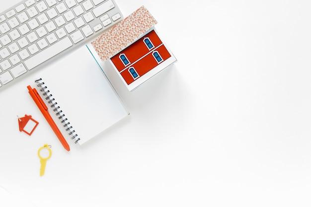 Diario in bianco con modello di casa in miniatura e tastiera su sfondo bianco