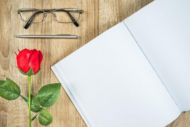 Diario in bianco del taccuino con il concetto del biglietto di s. valentino delle rose rosse
