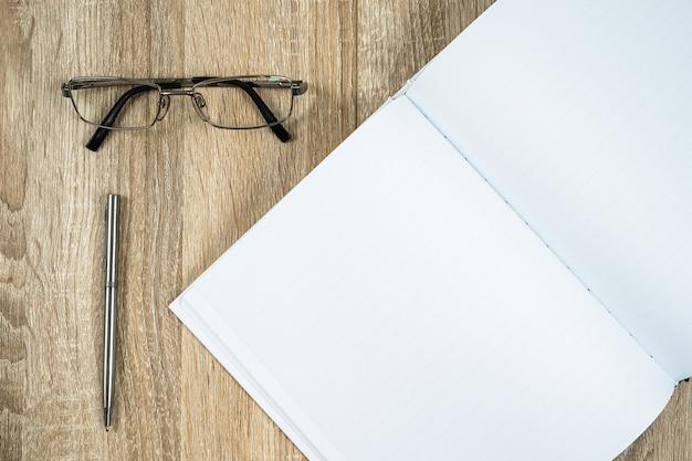 Diario in bianco del taccuino con la penna e gli occhiali d'argento