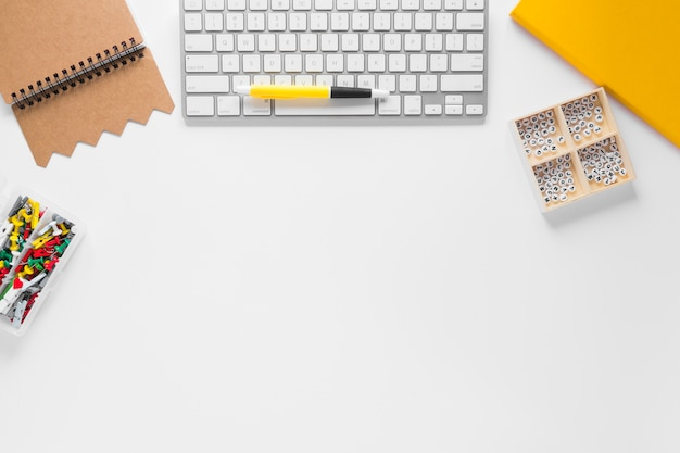 Diario; penna; tastiera; puntine da disegno e alfabeti nella casella sulla scrivania bianca