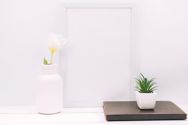 Diario; pianta; fiore del tulipano con cornice vuota sul tavolo bianco