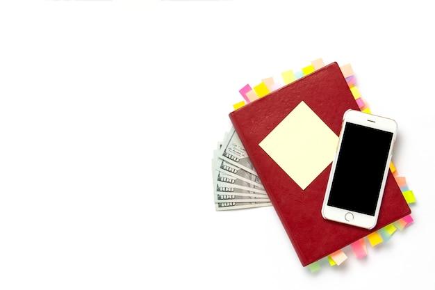 Diario rosso con adesivi sulle pagine, telefono bianco, banconote da cento dollari, sfondo bianco. concetto di business di successo, molti incontri e piani per un lungo periodo. vista piana, vista dall'alto