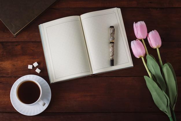 Diario, tazza con caffè, tulipani, libro sul tavolo di legno scuro