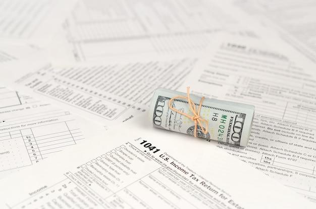 Dichiarazione dei redditi per gli stati e la fiducia forma con rotolo di banconote in dollari americani