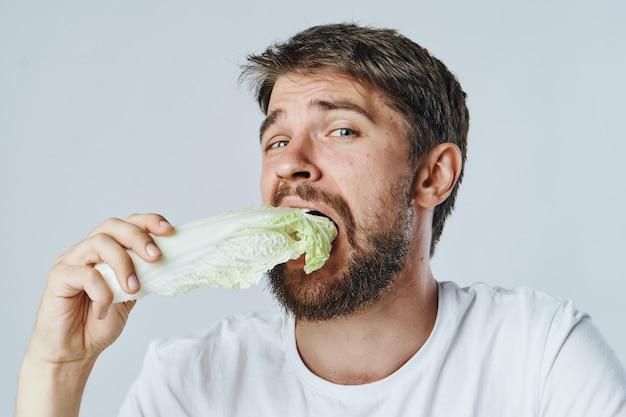Dieta alimentare l'uomo mangia cavolo in una maglietta bianca sana