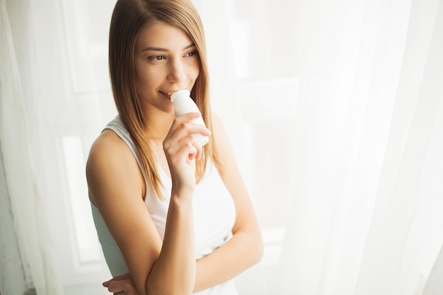 Dieta. bella donna in buona salute che beve yogurt naturale, prodotto lattiero-caseario