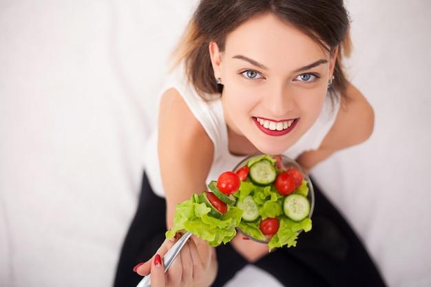 Dieta. bella giovane donna che mangia insalata di verdure