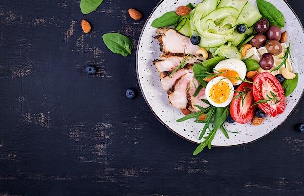 Dieta chetogenica. brunch di keto. uovo sodo, bistecca di maiale e olive, cetriolo, spinaci, brie, noci e pomodoro. vista dall'alto