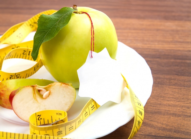 Dieta e cibo salutare. mela gialla, verde con foglia, nastro e adesivo