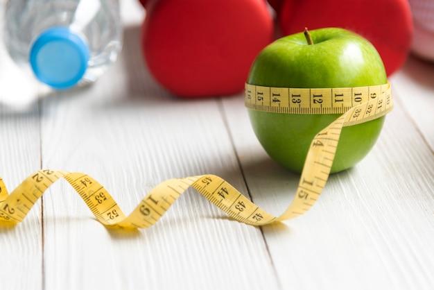 Dieta e concetto sano del peso di perdita di vita. mela verde e misura rubinetto con verdure fresche e attrezzature sportive per dimagrimento dieta donna