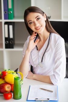 Dieta e concetto sano. nutrizionista sorridente nel suo ufficio