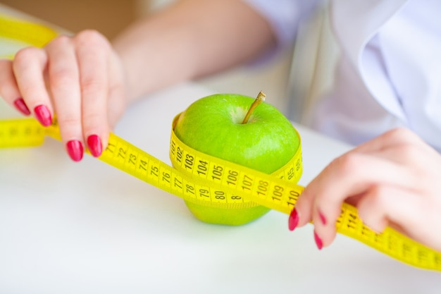 Dieta. fitness e concetto di dieta alimentare sana. dieta equilibrata con verdure. ritratto del dietista allegro di medico che misura mela verde nel suo ufficio. concetto di cibo naturale e stile di vita sano.
