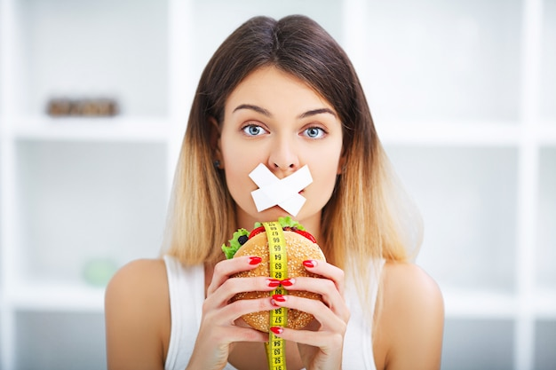 Dieta. giovane bella donna che mangia hamburger