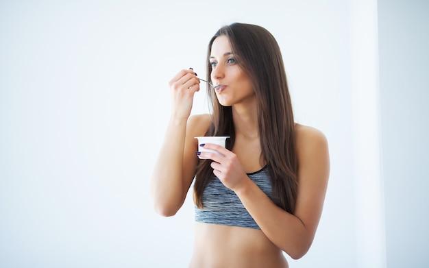 Dieta. giovane donna felice che mangia yogurt in cucina