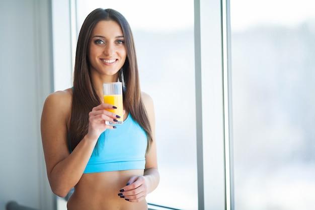 Dieta. giovane donna sorridente felice che beve il succo di arancia