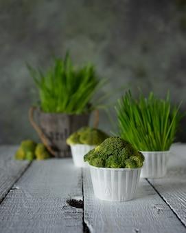 Dieta i bigné dai broccoli e dalle erbe freschi sulla tavola di legno bianca