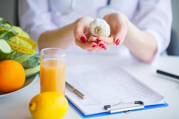 Dieta. il dottore nutritionist tiene l'aglio nel suo ufficio.