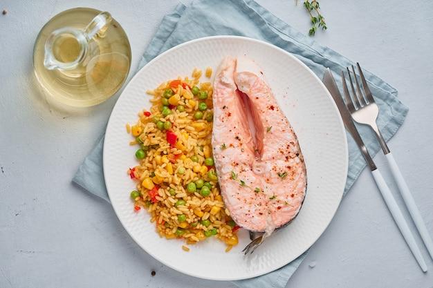 Dieta paleo, keto, fodmap. salmone al vapore e verdure, piatto bianco sul tavolo blu