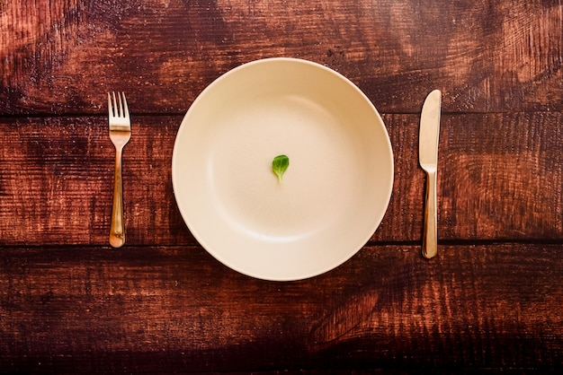 Dieta per perdere peso, immagine di piatto e posate con un po 'di verdura scarsa.